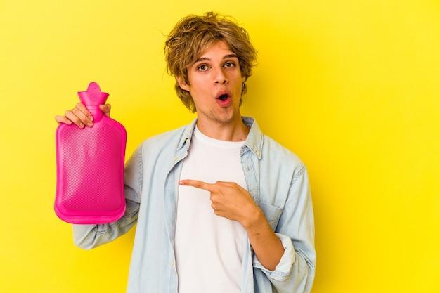 Młody kaukaski mężczyzna z makijażem trzyma gorącą torbę z wodą odizolowaną na żółtym tle, wskazując na bok