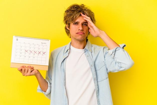 Młody kaukaski mężczyzna z makijażem trzyma kalendarz na białym tle na żółtym tle jest zszokowany, pamięta ważne spotkanie.