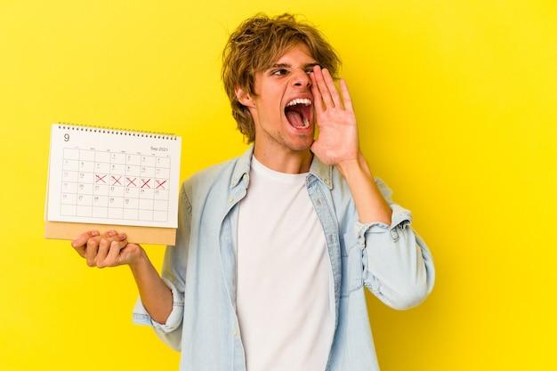 Młody kaukaski mężczyzna z makijażem trzyma kalendarz na białym tle na żółtym tle krzycząc i trzymając dłoń w pobliżu otwartych ust.
