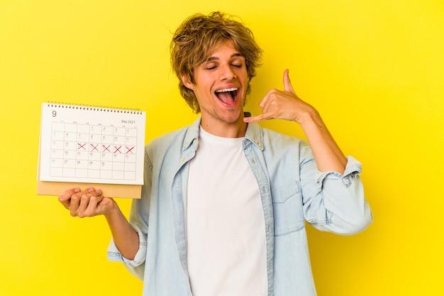 Młody kaukaski mężczyzna z makijażem trzyma kalendarz na białym tle na żółtym tle pokazując gest połączenia z telefonu komórkowego palcami.