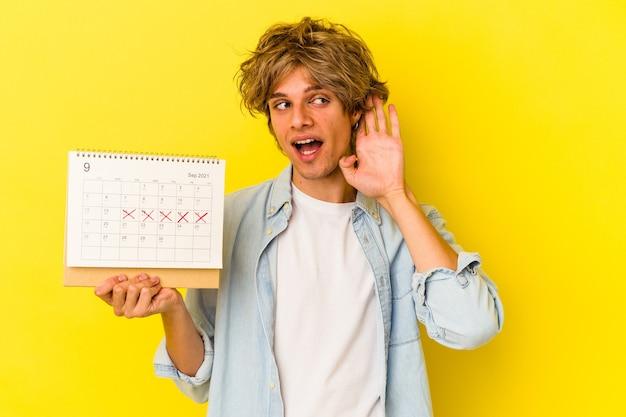 Młody kaukaski mężczyzna z makijażem trzyma kalendarz na białym tle na żółtym tle próbuje słuchać plotek.