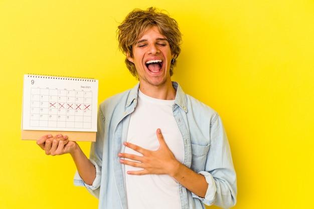 Młody kaukaski mężczyzna z makijażem trzyma kalendarz na białym tle na żółtym tle śmieje się głośno trzymając rękę na klatce piersiowej.