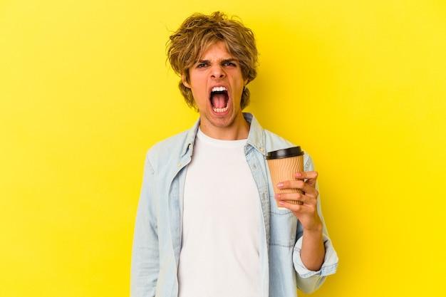 Młody kaukaski mężczyzna z makijażem trzyma kawę na wynos na białym tle na żółtym tle krzycząc bardzo zły i agresywny.