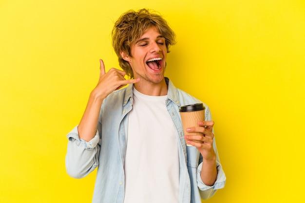 Młody kaukaski mężczyzna z makijażem trzyma kawę na wynos na białym tle na żółtym tle pokazując gest połączenia z telefonu komórkowego palcami.