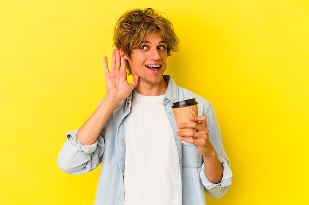 Młody kaukaski mężczyzna z makijażem trzyma kawę na wynos na białym tle na żółtym tle próbuje słuchać plotek.