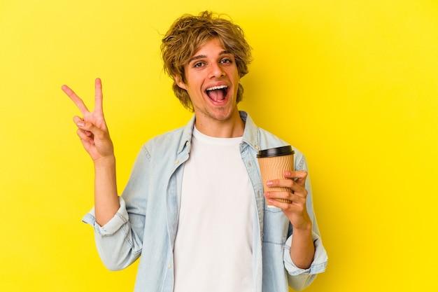 Młody kaukaski mężczyzna z makijażem trzyma kawę na wynos na białym tle na żółtym tle radosny i beztroski pokazując palcem symbol pokoju.