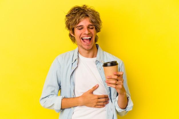Młody kaukaski mężczyzna z makijażem trzyma kawę na wynos na białym tle na żółtym tle śmiejąc się i bawiąc.