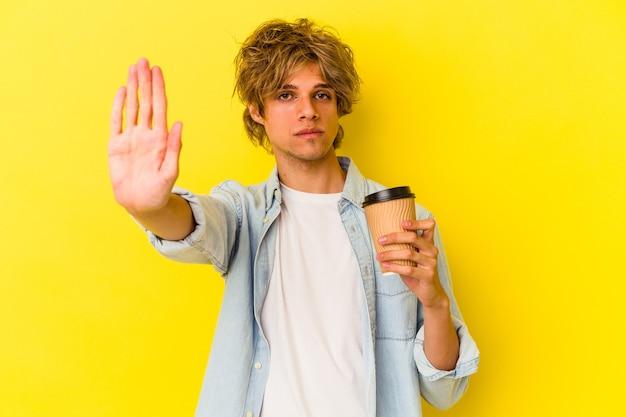 Młody kaukaski mężczyzna z makijażem trzyma kawę na wynos na białym tle na żółtym tle stojący z wyciągniętą ręką pokazując znak stop, uniemożliwiając.