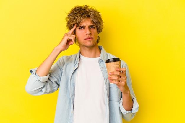 Młody kaukaski mężczyzna z makijażem trzyma kawę na wynos na białym tle na żółtym tle wskazując świątynię palcem, myśląc, koncentrując się na zadaniu.