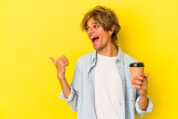 Młody kaukaski mężczyzna z makijażem trzyma kawę na wynos na białym tle na żółtym tle wskazuje palcem kciuka, śmiejąc się i beztrosko.