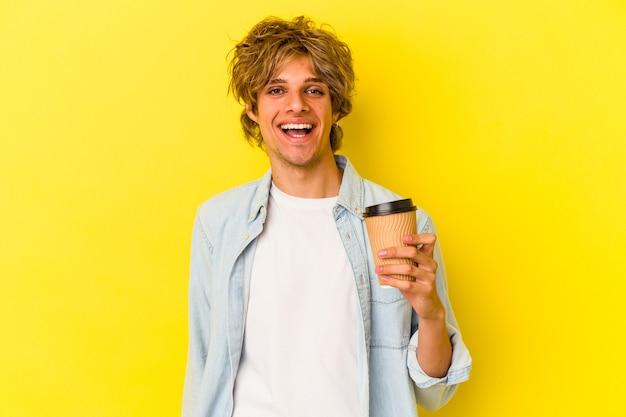 Młody kaukaski mężczyzna z makijażem trzyma kawę na wynos na żółtym tle szczęśliwy, uśmiechnięty i wesoły.