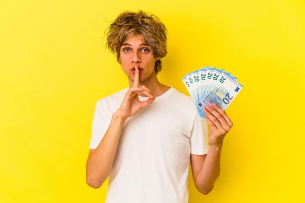 Młody kaukaski mężczyzna z makijażem trzyma rachunki na białym tle na żółtym tle, zachowując tajemnicę lub prosząc o ciszę.
