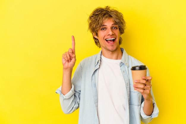 Młody kaukaski mężczyzna z makijażem, trzymając kawę na wynos na białym tle na żółtym tle pokazując numer jeden palcem.
