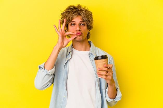 Młody kaukaski mężczyzna z makijażem, trzymając kawę na wynos na białym tle na żółtym tle z palcami na ustach zachowując tajemnicę.