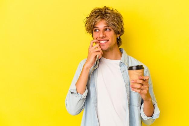 Młody kaukaski mężczyzna z makijażem trzymając kawę na wynos na żółtym tle zrelaksowany myśląc o czymś patrząc na miejsce.