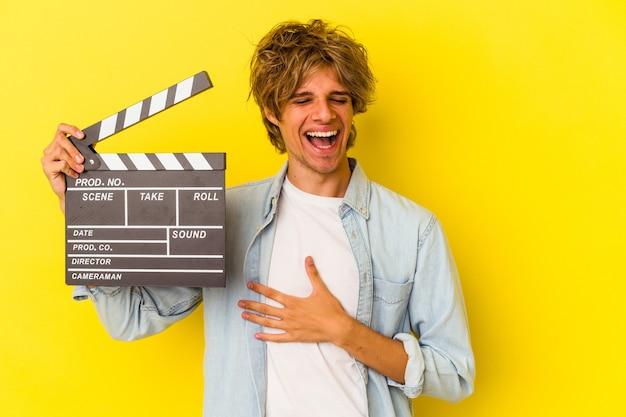 Młody kaukaski mężczyzna z makijażem trzymając klaps na białym tle na żółtym tle śmieje się głośno trzymając rękę na klatce piersiowej.
