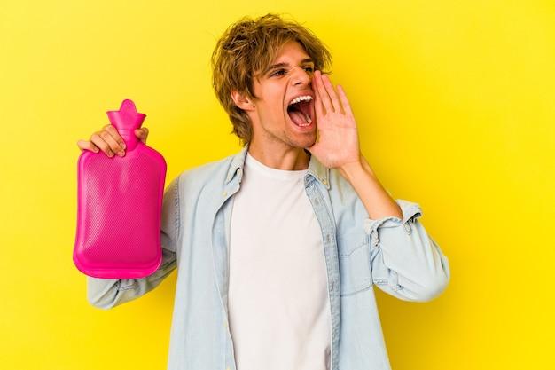 Młody kaukaski mężczyzna z makijażem, trzymając worek gorącej wody na białym tle na żółtym tle krzycząc i trzymając dłoń w pobliżu otwartych ust.