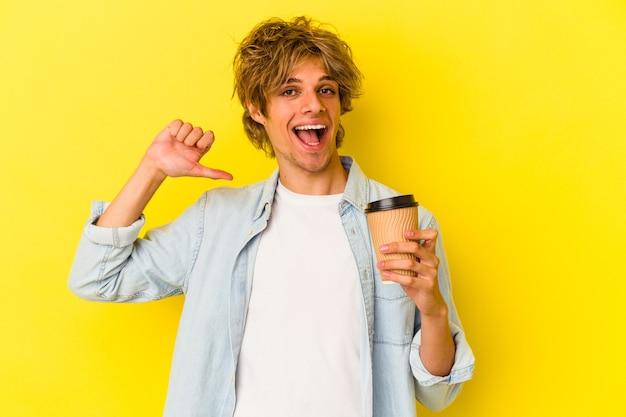 Młody kaukaski mężczyzna z makijażem trzymający kawę na wynos na żółtym tle czuje się dumny i pewny siebie, przykład do naśladowania.