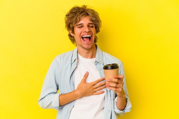 Młody kaukaski mężczyzna z makijażem trzymający kawę na wynos na żółtym tle śmieje się głośno trzymając rękę na klatce piersiowej.