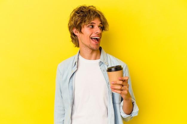 Młody kaukaski mężczyzna z makijażem trzymający kawę na wynos na żółtym tle wygląda na bok uśmiechnięty, wesoły i przyjemny.