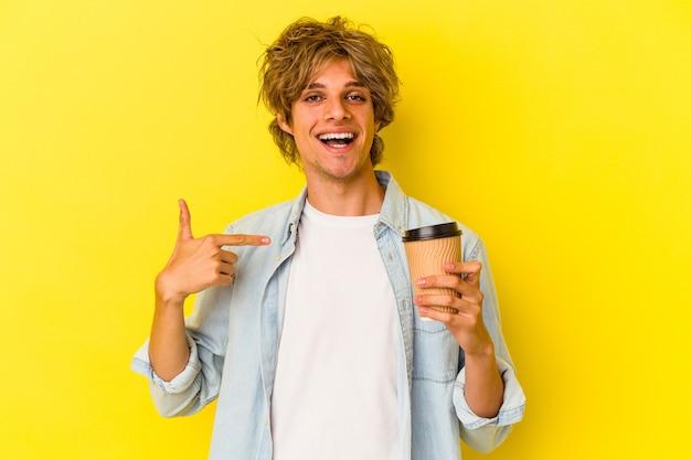 Młody kaukaski mężczyzna z makijażem trzymający kawę na wynos odizolowaną na żółtym tle osoba wskazująca ręcznie na miejsce na koszulkę, dumna i pewna siebie