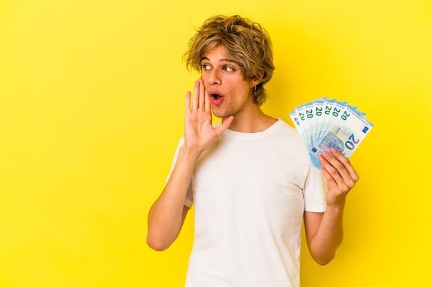 Młody kaukaski mężczyzna z makijażem trzymający rachunki na żółtym tle mówi tajne gorące wiadomości o hamowaniu i patrzy na bok