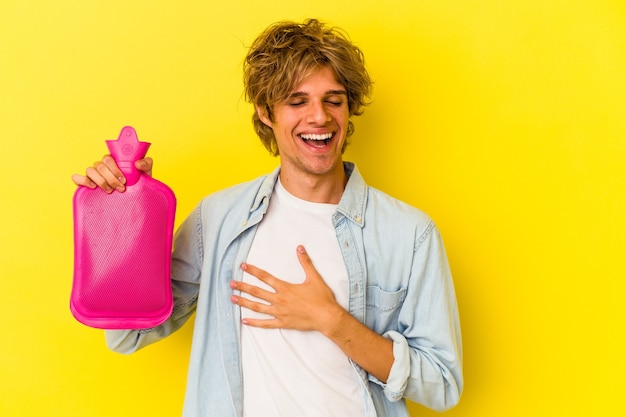 Młody kaukaski mężczyzna z makijażem, trzymający worek gorącej wody na żółtym tle, śmieje się głośno trzymając rękę na klatce piersiowej.