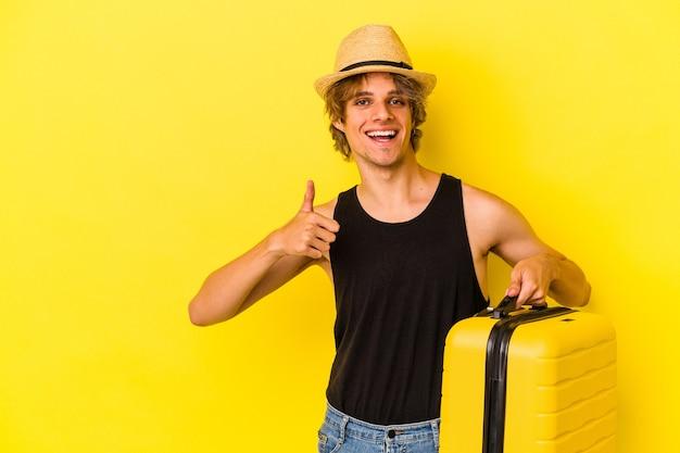 Młody kaukaski mężczyzna z makijażem zamierza podróżować na białym tle na żółtym tle, uśmiechając się i podnosząc kciuk w górę
