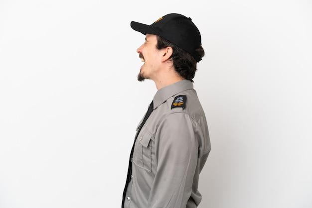 Młody kaukaski mężczyzna z ochrony na białym tle śmiejący się w pozycji bocznej