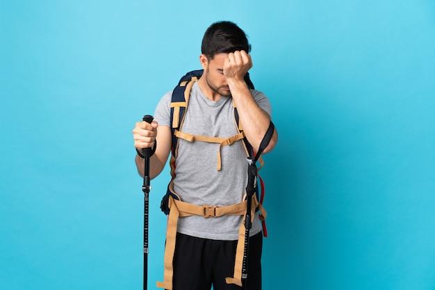 Młody kaukaski mężczyzna z plecakiem i kijkami trekkingowymi na białym tle na niebieskiej ścianie z bólem głowy