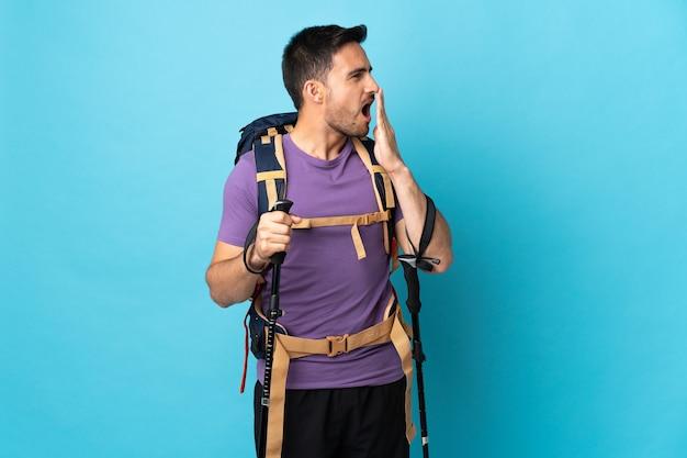 Młody kaukaski mężczyzna z plecakiem i kijkami trekkingowymi odizolowanymi na niebiesko, ziewając i obejmując ręką szeroko otwarte usta
