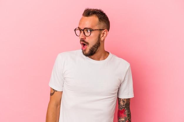 Młody kaukaski mężczyzna z tatuażami na białym tle na różowym tle jest zszokowany z powodu czegoś, co widziała.