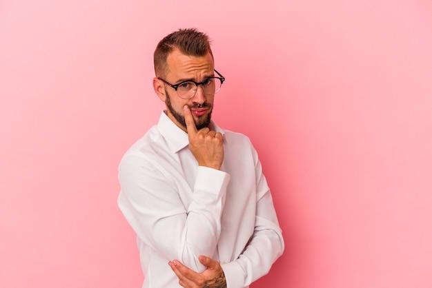 Młody kaukaski mężczyzna z tatuażami na białym tle na różowym tle kontemplując, planując strategię, myśląc o sposobie prowadzenia biznesu.