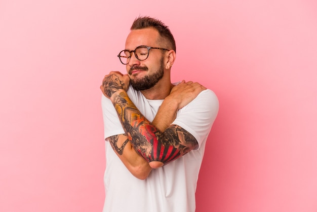 Młody kaukaski mężczyzna z tatuażami na białym tle na różowym tle przytula się, uśmiechając się beztrosko i szczęśliwy.