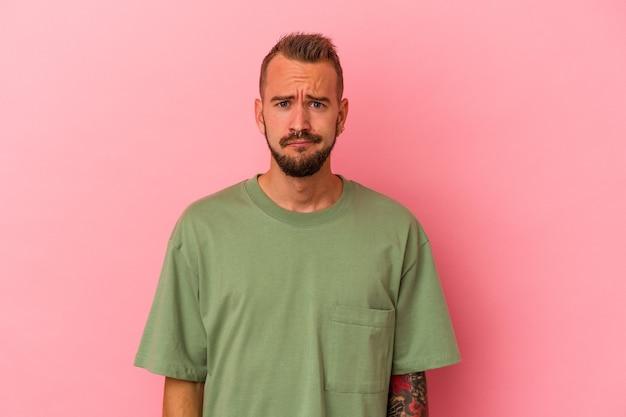 Młody kaukaski mężczyzna z tatuażami na białym tle na różowym tle smutna, poważna twarz, czuje się nieszczęśliwa i niezadowolona.