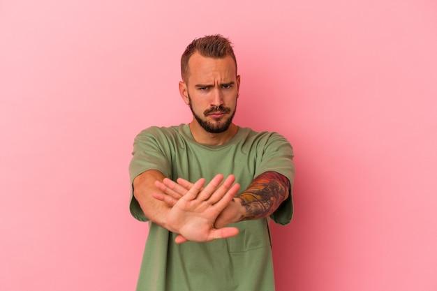 Młody kaukaski mężczyzna z tatuażami na białym tle na różowym tle stojący z wyciągniętą ręką pokazując znak stop, uniemożliwiając.