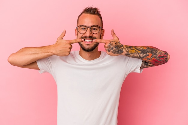 Młody kaukaski mężczyzna z tatuażami na białym tle na różowym tle uśmiecha się, wskazując palcami na usta.