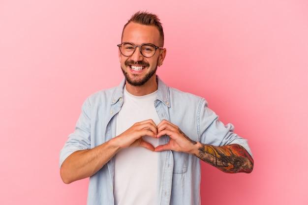 Młody kaukaski mężczyzna z tatuażami na białym tle na różowym tle uśmiechający się i pokazujący kształt serca rękami.