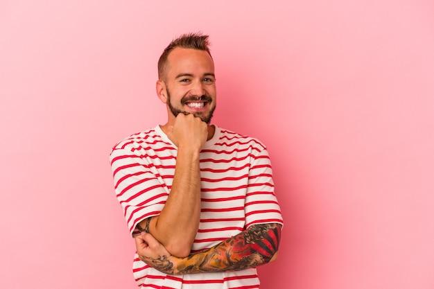 Młody kaukaski mężczyzna z tatuażami na białym tle na różowym tle uśmiechnięty szczęśliwy i pewny siebie, dotykając podbródka ręką.