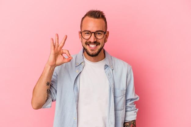 Młody kaukaski mężczyzna z tatuażami na białym tle na różowym tle wesoły i pewny siebie pokazując ok gest.