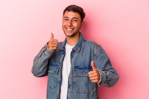 Młody kaukaski mężczyzna z tatuażami na białym tle na żółtym tle podnosząc kciuki do góry, uśmiechnięty i pewny siebie.