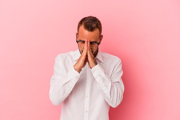 Młody kaukaski mężczyzna z tatuażami na różowym tle modlący się, okazujący oddanie, osoba religijna szukająca boskiej inspiracji.