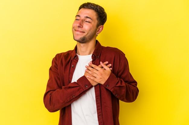 Młody kaukaski mężczyzna z tatuażami na żółtym tle ma przyjazny wyraz, przyciskając dłoń do klatki piersiowej. koncepcja miłości.