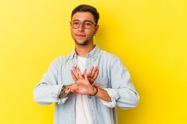 Młody kaukaski mężczyzna z tatuażami na żółtym tle robi gest odmowy