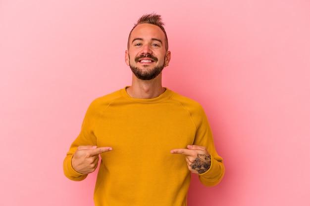 Młody kaukaski mężczyzna z tatuażami odizolowanymi na różowym tle osoba wskazująca ręcznie na miejsce na koszulkę, dumna i pewna siebie