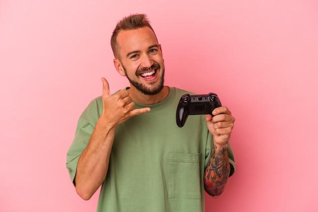 Młody kaukaski mężczyzna z tatuażami, trzymając kontroler gier na białym tle na różowym tle pokazujący gest połączenia z telefonem komórkowym palcami.