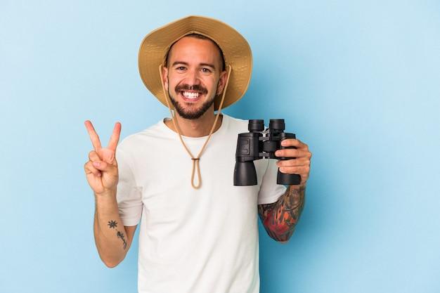 Młody kaukaski mężczyzna z tatuażami, trzymając lornetkę na białym tle na niebieskim tle wyświetlono numer dwa palcami.