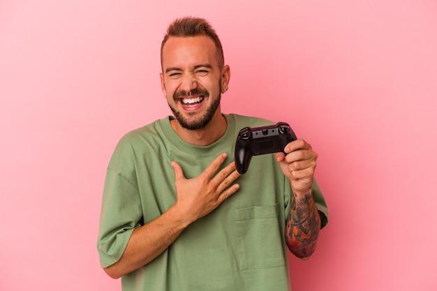 Młody kaukaski mężczyzna z tatuażami, trzymający kontroler gier na białym tle na różowym tle, śmieje się głośno, trzymając rękę na klatce piersiowej.