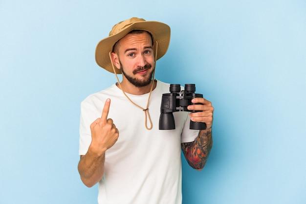 Młody kaukaski mężczyzna z tatuażami, trzymający lornetkę na białym tle na niebieskim tle, wskazując palcem na ciebie, jakby zapraszając podejdź bliżej.