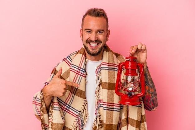 Młody kaukaski mężczyzna z tatuażami trzymający vintage latarnię na białym tle na różowym tle osoba wskazująca ręcznie na miejsce na koszulkę, dumna i pewna siebie